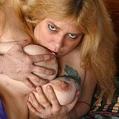 Tatooed corpulent blond bonks herself with a dildo.
