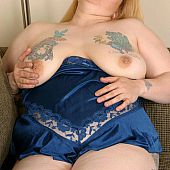 Tatooed large plumper takes off clothes.